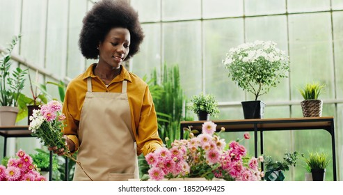 Portrait of African American happy woman flower store manager making bouquet at workplace indoor. Young female florist entrepreneur working with flowers in floral center. Floristry concept