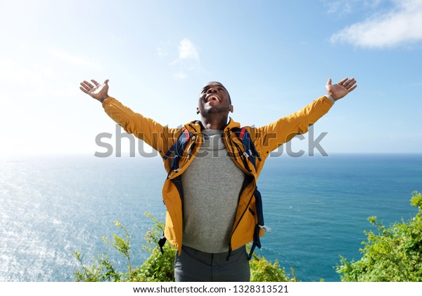 Portrait of african american male hiker with backpack and arms open