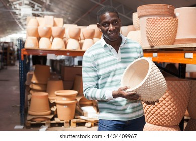 Portrait of African American man choosing pots for flowers and trees in gardening market