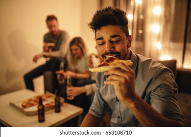 Portrait of an african american man enjoying eating pizza with friends.
