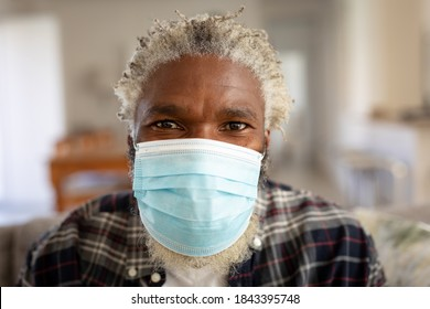 Portrait of African American man at home, wearing a mask and looking to camera. Social distancing and self isolating at home during Coronavirus Covid 19 quarantine lockdown.