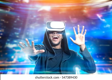 Portrait of an African American man in a hoodie and vr glasses playing an exciting game. Concept of the future is here. Toned image. Mock up