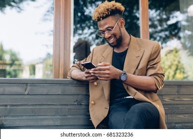 A portrait of African American man in jacket and glasses with smartphone sitting near the windows