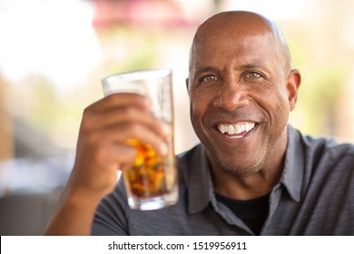 Portrait of an African American man at a restaurant having a drink.