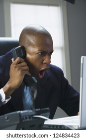 Portrait of African American man shouting while talking on phone