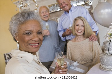 Portrait of an African American senior woman holding glass of champagne with friends in he background