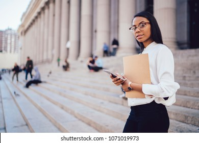 Portrait of african american student of faculty of law with folder checking mail on smartphone while looking at camera standing near university building.Dark skinned female lawyer with telephone