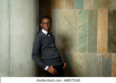Portrait of an African American teen boy leaning on a pillar in front of a green and yellow tile wall.  He is wearing a sweater and bowtie.