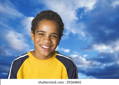 Portrait of an African American teenage boy against a beautiful blue sky with white clouds