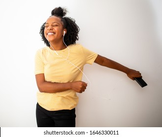 Portrait african american teenage girl listening to music with cellphone and earphones against isolated white background and dancing