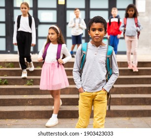 Portrait of African american tweenager walking outside school building on autumn day, going to lessons.