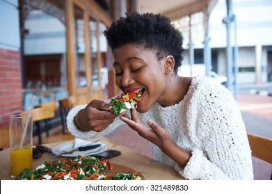 Portrait of an african american woman eating pizza at outdoor restaurant