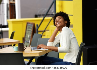 Portrait of an african american woman laughing with laptop at cafe