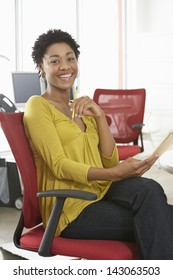 Portrait of African American woman with pencil and notepad sitting on office chair