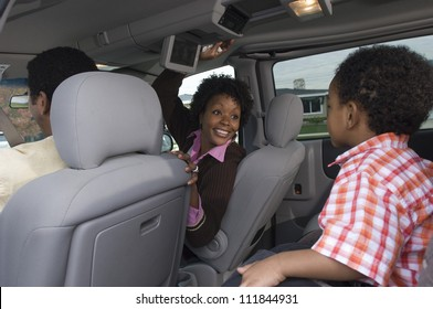 Portrait of an African American woman sitting in car with small boy in foreground