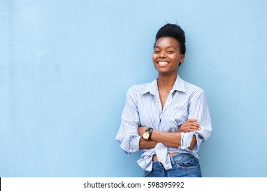 Portrait of african american woman smiling with arms crossed on blue background
