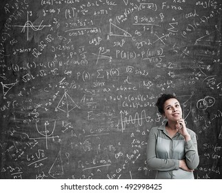 Portrait of African American woman solving a difficult task standing near blackboard with formulas. Concept of science. Mock up