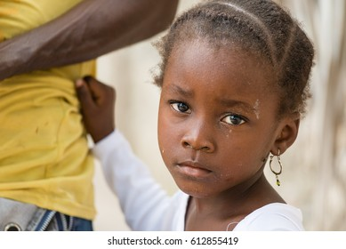Portrait of African black little girl looking at camera and holding dad's shirt