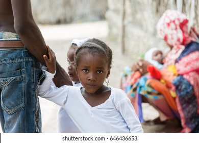 Portrait of African black little girl looking at camera and holding dad's hand.Mother holding baby in the background