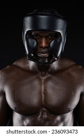Portrait of african boxer wearing protective head guard against black background. Muscular man wearing boxing helmet.