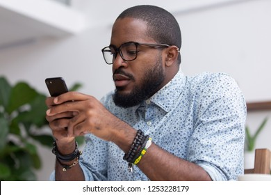 Portrait of african businessman company owner sitting in office room holding smartphone chatting online with friend or surfing internet checking email and social networks. Wireless technology concept