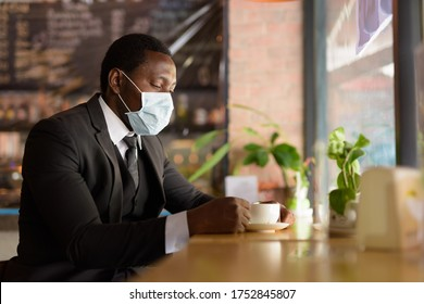 Portrait of African businessman wearing mask while drinking coffee inside the coffee shop as the new normal