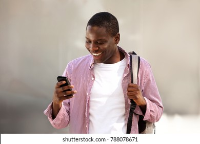 Portrait of african college student standing outside with bag and reading text message on mobile phone
