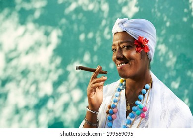 Portrait of african cuban woman smoking cohiba cigar and looking at camera smiling