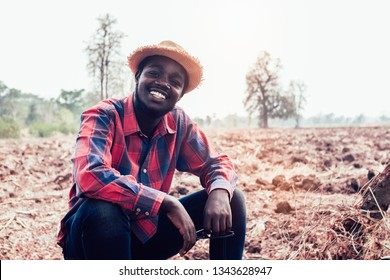 Portrait of african farmer man sitting at the field
