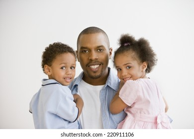 Portrait of African father holding children