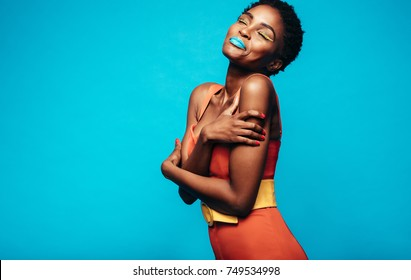 Portrait of african female model with vivid makeup hugging herself against blue background. Beautiful young woman with vibrant makeup and eyes closed.