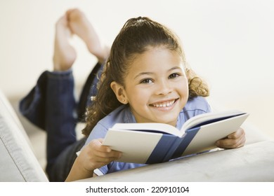 Portrait of African girl holding book on sofa