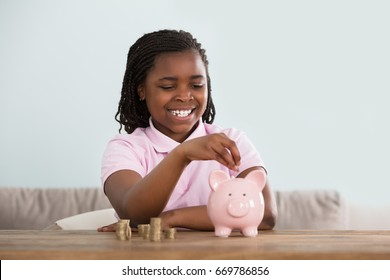 Portrait Of An African Girl Inserting Coins In Pink Piggy Bank On Table