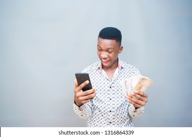 Portrait of a African guy looking at his mobile phone after receiving good news with bunch of Nigeria money on his hands