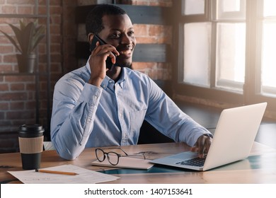 Portrait of African guy talking on phone with laptop in front of him on table