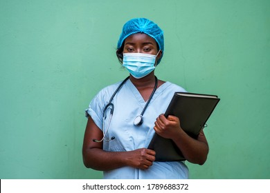 Portrait of an African health care provider holding patient documents and stethoscope around neck,wearing face mask and head gear for protection