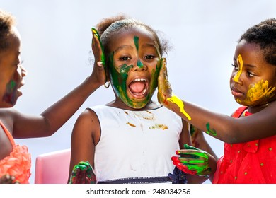 Portrait of African kids painting themselves with color paint.Isolated against light background.
