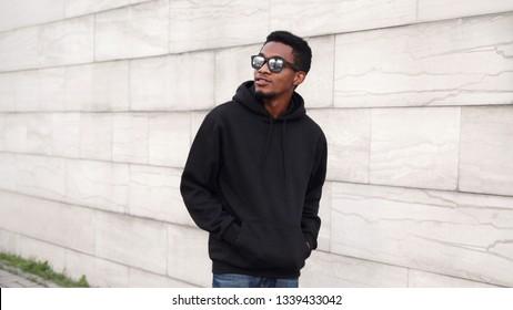 Portrait african man in black hoodie, sunglasses walking on city street looking away over gray brick wall background