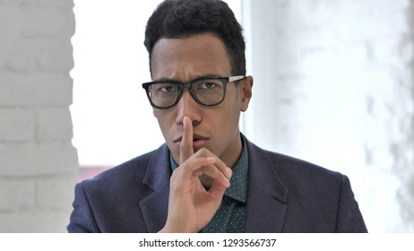 Portrait of African Man Gesturing  Silence, Finger on Lips