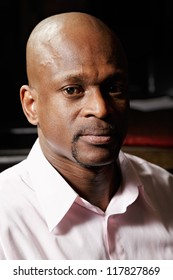 Portrait of african man in pink shirt looking to camera