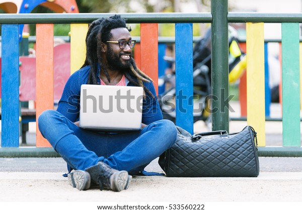 Portrait of african man sitting outside with laptop. Urban work Concept