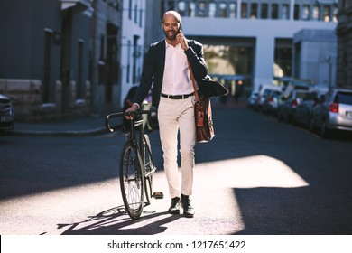 Portrait of african man walking with bicycle to work and talking on phone. Business man going to office with his bike.