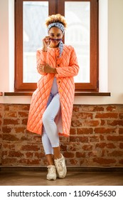 Portrait of an African model woman in orange spring jacket and blue pants against the background of the window