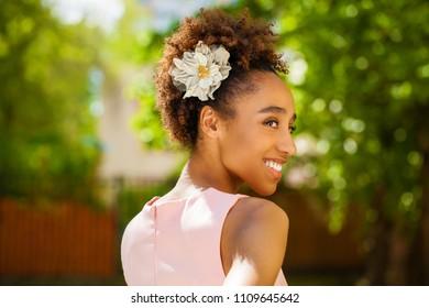Portrait of an African model woman in pink dress, summer park outdoor