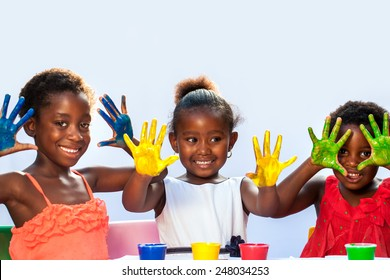 Portrait of African threesome showing painted hands.Isolated against light background.