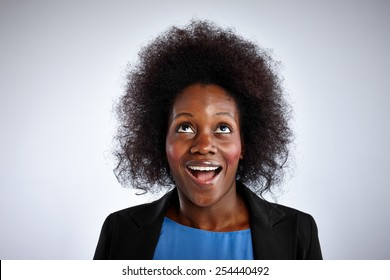 Portrait of african woman with curly hair looking up laughing against white background