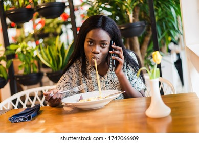 Portrait of african woman eating spaghetti pasta and talking on the Phone
