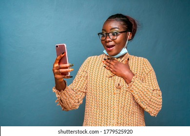 Portrait of an African woman wearing surgical face mask for protection,holding her phone and looking surprised and cheerful,isolate on a blue background