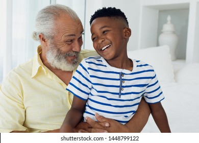 Portrait of African-American child and grandfather smiling together in a room. Authentic Senior Retired Life Concept