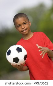 Portrait of African-American child holding soccer ball.